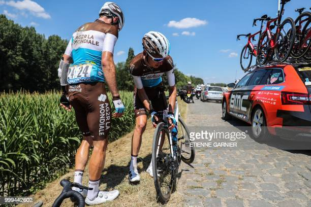 France's Romain Bardet assisted by his France's AG2R La Mondiale cycling team teammates Switzerland's Mathias Frank changes wheel after suffering a...