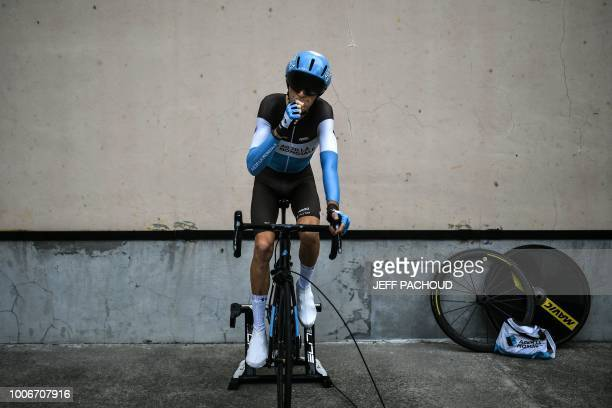 TOPSHOT France's Romain Bardet eats a snack as he trains on a stationary bicycle prior to take the start of the 20th stage of the 105th edition of...
