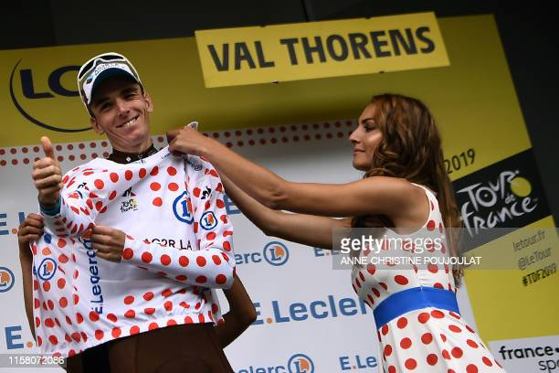 France's Romain Bardet is helped to put on his best climber's polka dot jersey on the podium of the twentieth stage of the 106th edition of the Tour...