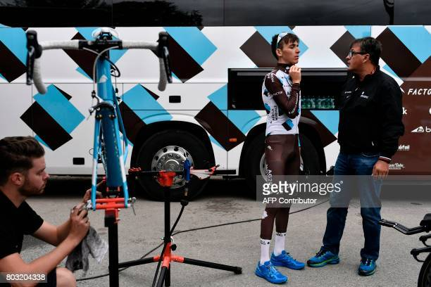 France's Romain Bardet speaks with a staff member next to a mechanic prior to a training session of the France's AG2R La Mondiale cycling team in...
