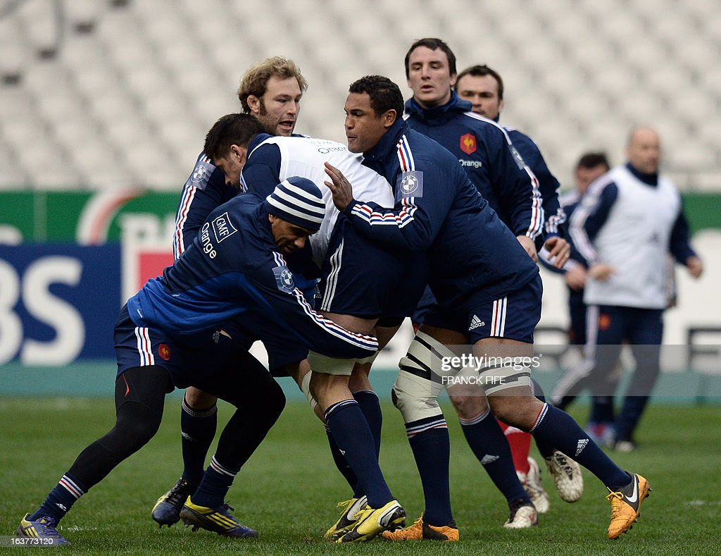 France's rugby union national team captain Thierry Dusautoir (R) vies with lock Christophe Samson (C) next to centre Wesley Fofana during the team's training session, on March 15, 2013 at the Stade...