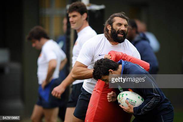 France's rugby union national team lock Sebastien Chabal and fullback Clement Poitrenaud share a joke during a training session 03 October 2007 in...