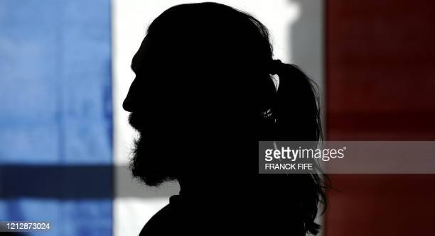 France's rugby union national team lock Sebastien Chabal is silhouetted as he takes part in a press conference in Wellington on June 17, 2009 as the...
