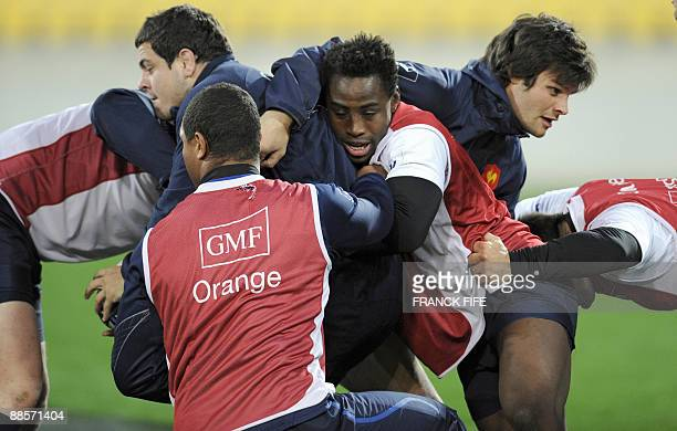 France's rugby union national team players Guilhem Guirado flanker Fulgence Ouedraoggo flanker Julien Puricelli practice a maul during a training...