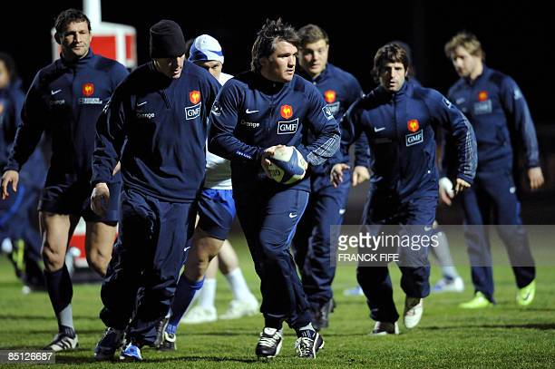 France's rugby union national team prop Sylvain Marconnet runs with a ball next to his teammates during a training session on February 26 2009 in...