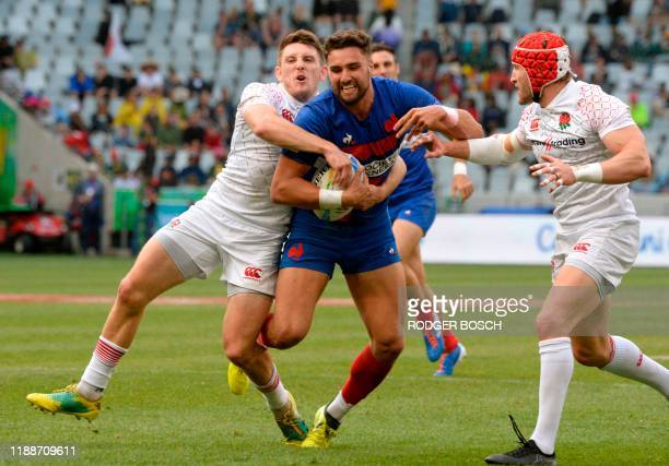 France's Sacha Valleau is tackled during the Cape Town leg of the World Rugby Sevens Series rugby match between England and France on December 14...