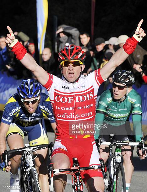 France's Samuel Dumoulin raises his arms in victory as he crosses the finish line of the Etoile of Besseges cycling race third stage on February 4...