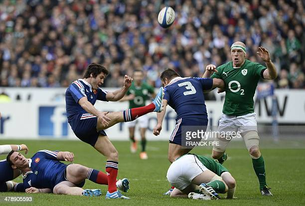 France's scrum half Maxime Machenaud kicks the ball next to France's prop Nicolas Mas and Ireland's lock Paul O'Connell during the Six Nations rugby...
