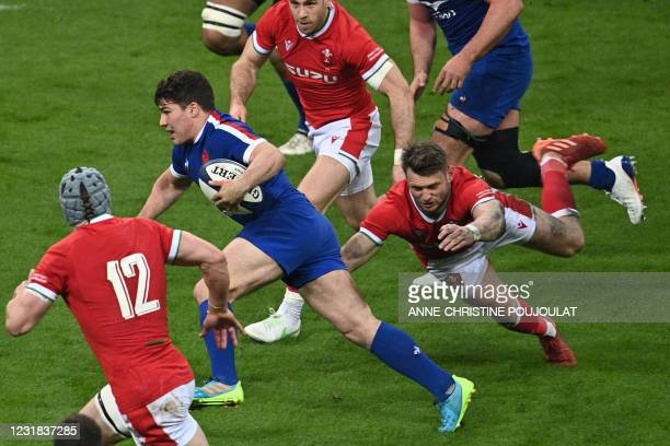 France's scrum-half Antoine Dupont runs to evade Wales' fly-half Dan Biggar during the Six Nations rugby union tournament match between France and...