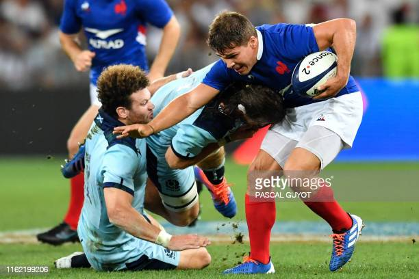 France's scrum-half Antoine Dupont runs with the ball as Scotland's lock Ben Toolis and Scotland's center Duncan Taylor attempt to tackle him during...