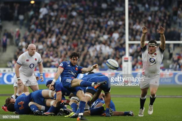 France's scrumhalf Maxime Machenaud kicks the ball as England's hooker Jamie George reaches to block it during the Six Nations international rugby...