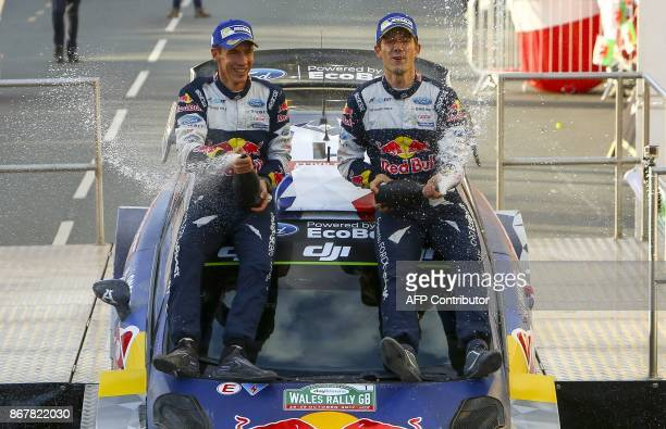 TOPSHOT France's Sebastien Ogier with codriver Julien Ingrassia spay champagne as they celebrate on top of their Ford Fiesta WRC after winning the...