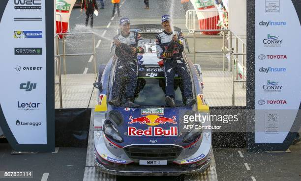 France's Sebastien Ogier with codriver Julien Ingrassia spay champagne as they celebrate on top of their Ford Fiesta WRC after winning the 2017 World...