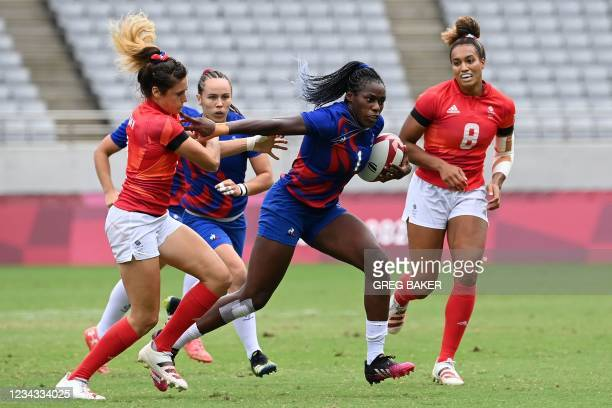 France's Seraphine Okemba breaks away from Britain's Abbie Brown and Celia Quansah to score a try during the women's rugby sevens semi-final match...
