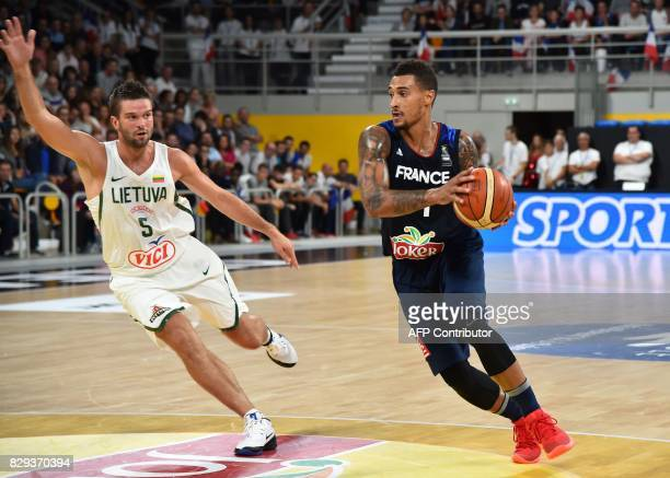 France's shooting guard Edwin Jackson runs with the ball followed by Lituania's point guard Mantas Kalnietis during a friendly basketball match...