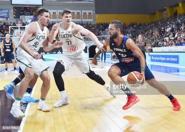 France's shooting guard Evan Fournier vies with Lituanie's forward Edgaras Ulanovas and forward Arturas Gudaitis during a friendly basketball match...