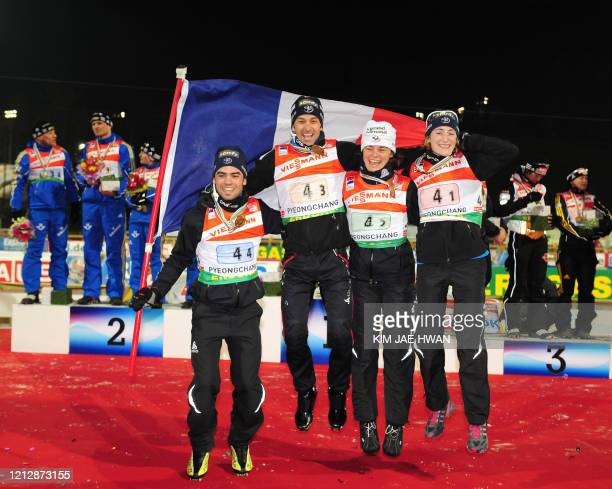 France's Simon Fourcade Vincent Defrasne Sylvie Becaert and Marie Laure Brunet celebrate after the awarding ceremony of the mixed relay at the IBU...
