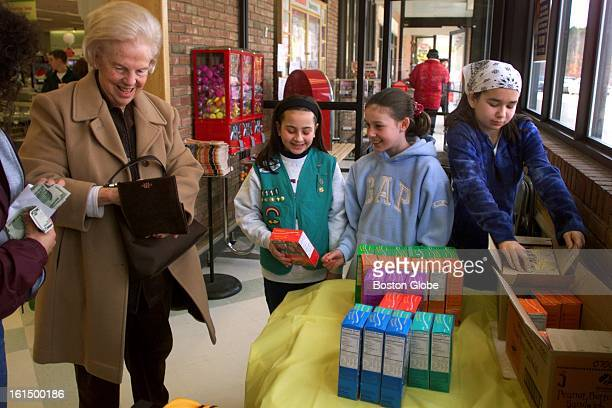 Frances Spillane left from Foxborough reaches in her pocketbook for cash to pay for girls scouts cookies she just bought from Junior Troop 1111 from...