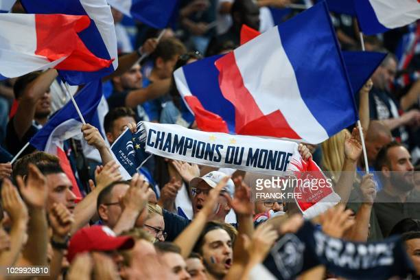 A France's supporter holds a scarf reading World Champions as he stands among fans waving French national flags and cheering for their team ahead of...