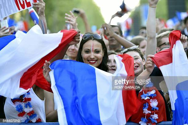 A France's supporter holds the French National flag as she watches the Euro 2016 quarterfinal football match between France and Iceland at the fan...