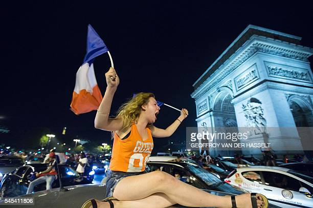 TOPSHOT France's supporters celebrate after France won the Euro 2016 semifinal football match against Germany on the Avenue des ChampsElysees in...