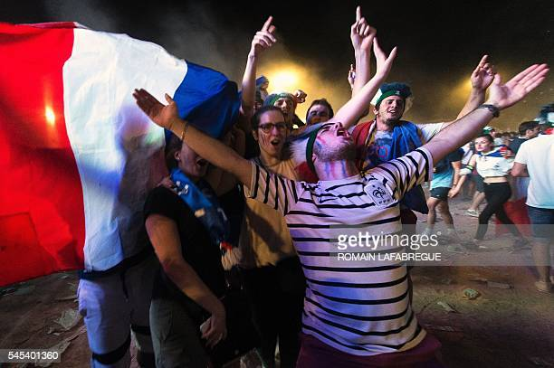 TOPSHOT France's supporters celebrate with a French flag at the fan zone in Lyon on July 7 2016 after France won the Euro 2016 semifinal football...