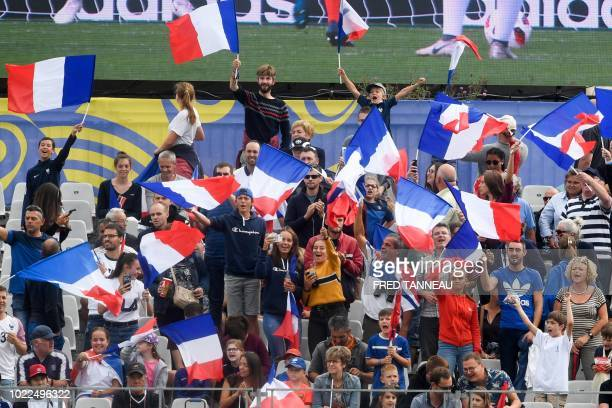 France's supporters cheer their team and wave French national flags during the Women's U20 World Cup 3rd place football match between France and...
