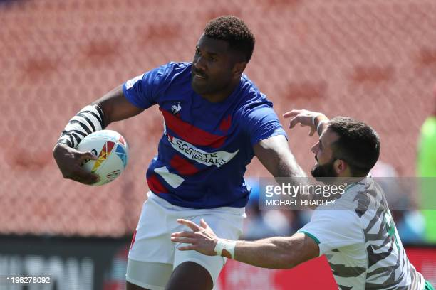 France's Tavite Veredamu fends off the tackle during the men's rugby sevens match between France and Ireland during day two of the HSBC World Rugby...