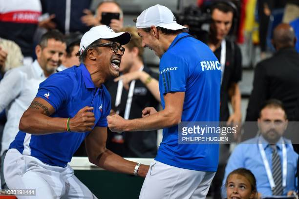 TOPSHOT France's team captain Yannick Noah celebrates with France's Lucas Pouille after victory in his singles match against Spain's Roberto...