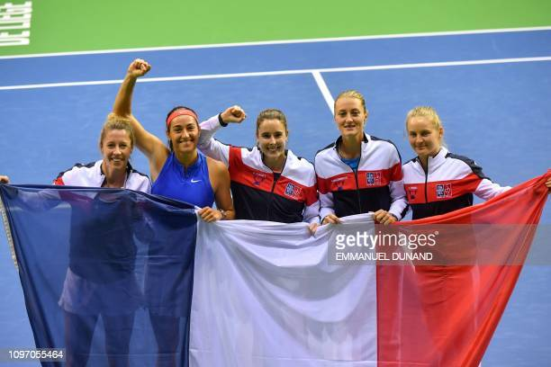 France's team players Pauline Parmentier Caroline Garcia Alize Cornet Kristina Mladenovic and Fiona Ferro celebrate with a French flag after France's...
