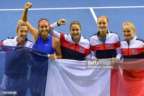 France's team players Pauline Parmentier Caroline Garcia Alize Cornet Kristina Mladenovic and Fiona Ferro celebrate with a French flag after France's...