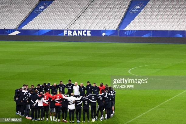 France's teammates gather for a minute of silent to pay a tribute to the victims of Paris' attack of the November 13 2015 at the start of a training...