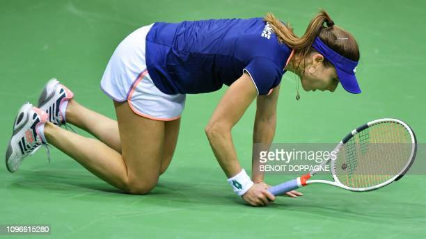 France's tennis player Alize Cornet falls during her first set of the FedCup World Group first round tennis match against Belgium's Elise Mertens in...
