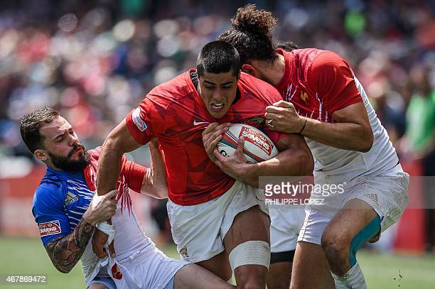 France's Terry Bouhraoua tries to tackle Argentina's Axel Muller during a match between France and Argentina on the second day of the rugby sevens...