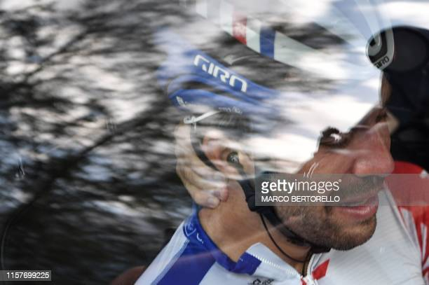 France's Thibaut Pinot, in his team car, reacts after quitting the Tour de France due to a thigh problem during the nineteenth stage of the 106th...