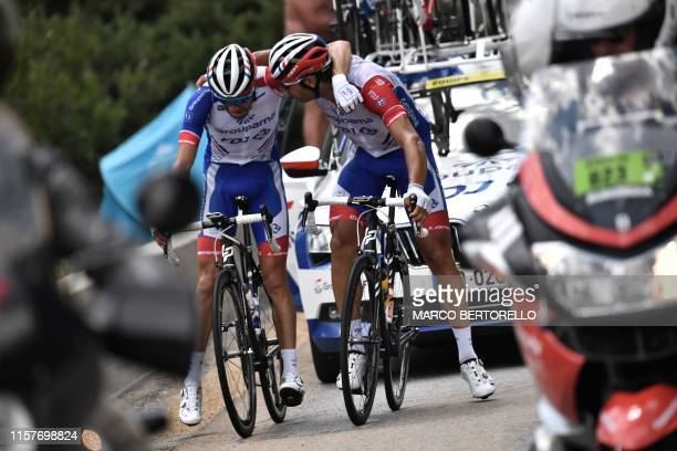 France's Thibaut Pinot is comforted by teammate France's William Bonnet as he stops, forced to quit the Tour due to pain in his left leg during the...