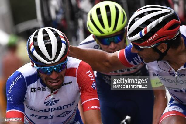 France's Thibaut Pinot is comforted by teammate France's William Bonnet as he suffers pain in his left leg during the nineteenth stage of the 106th...