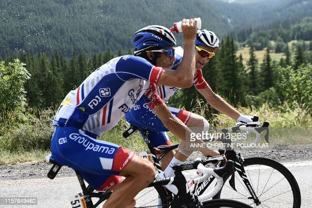 France's Thibaut Pinot , past his teammate France's Matthieu Ladagnous, pours water on his head as a heat wave hit Western Europe during the...