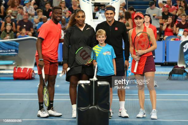 Frances Tiafoe and Serena Williams of the United States stand with Roger Federer and Belinda Bencic of Switzerland following the coin toss before the...