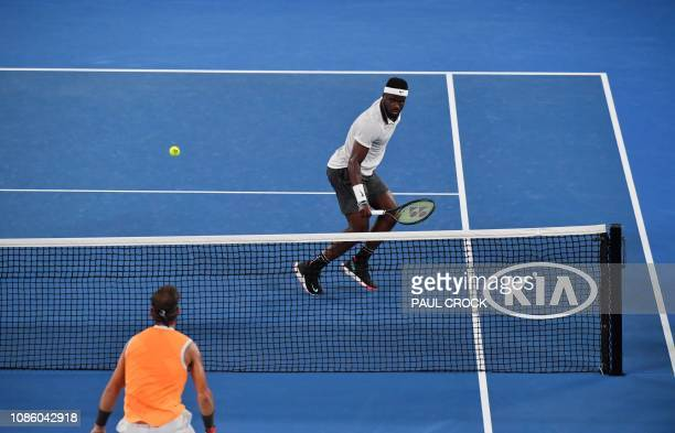 Frances Tiafoe of the US and Spain's Rafael Nadal eye the ball during their men's singles quarterfinal match on day nine of the Australian Open...