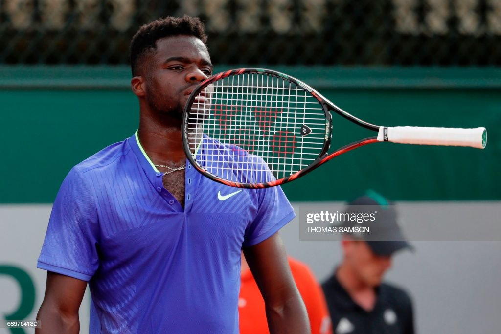 US Frances Tiafoe throws his racket as reacts after a point against Italy's Fabio Fognini during their tennis match at the Roland Garros 2017 French Open on May 29, 2017 in Paris. / AFP PHOTO / Thomas SAMSON