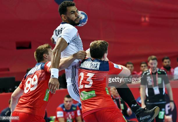 France's Timothey N'Guessan vies for the ball with Norway's Espen Lie Hansen and Goran Sorheim during the preliminary round group B match of the...