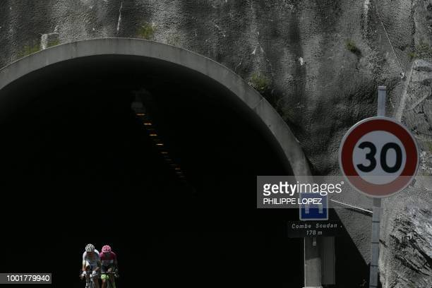 TOPSHOT France's Warren Barguil and France's Pierre Rolland exit a tunnel as they ride in a counter attack group during the twelfth stage of the...