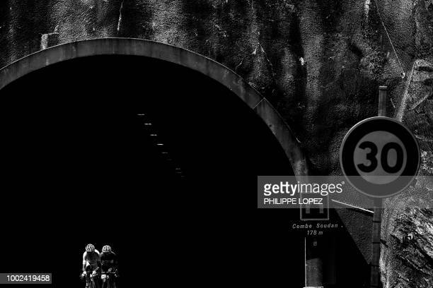 France's Warren Barguil and France's Pierre Rolland exit a tunnel as they ride in a counter attack group during the twelfth stage of the 105th...