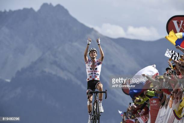 TOPSHOT France's Warren Barguil wearing the best climber's polka dot jersey celebrates as he crosses the finish line at the end of the 1795 km...