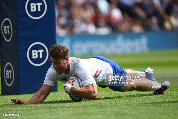 France's wing Damian Penaud dives over the line to score their early first try during the international Test rugby union match between Scotland and...