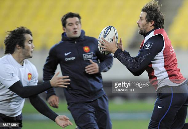 France's winger Cedric Heymans runs with a ball in front scrumhalf Alexis Palisson and Florian Fritz during a training session at the Westpac Stadium...