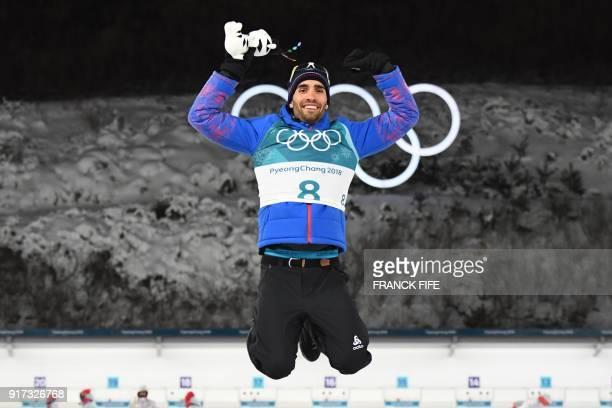 TOPSHOT France's winner Martin Fourcade jumps on the podium during the victory ceremony after competing in the men's 125km pursuit biathlon event...