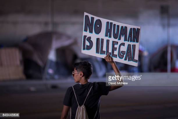 A marcher passes the tents of homeless people at an encampment in an underpass as thousands of immigrants and supporters join the Defend DACA March...