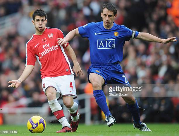 Francesc Fabregas of Arsenal holds off Gary Neville of Manchester United as he passes to Samir Nasri to score their second goal during the Barclays...